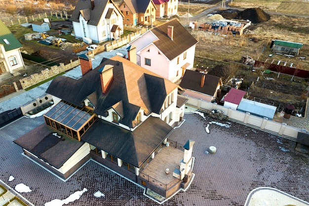 Aerial top view of new residential house cottage with shingle roof on fenced big yard on sunny day.