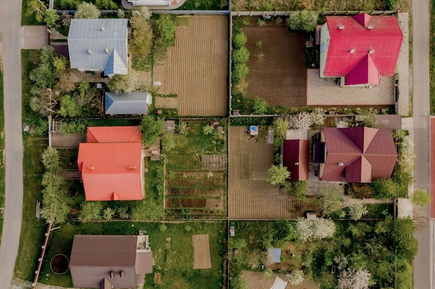 コンクリートの基礎床と緑の草の芝生と舗装された庭のある家の空中のトップビュー