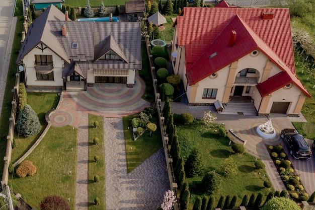 Вид с воздуха на частный дом, вымощенный двор с зеленой лужайкой и бетонным фундаментным полом.