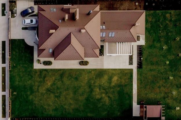 Вид сверху частного дома с мощеным двором и зеленой лужайкой с бетонным фундаментным полом.
