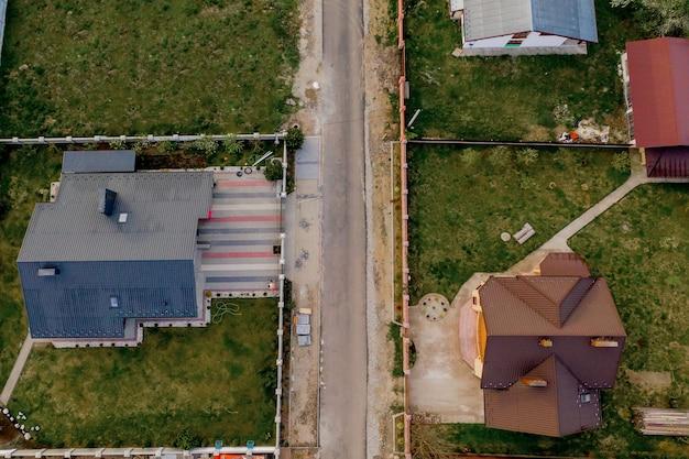 コンクリート基礎床と緑の芝生の芝生と舗装された庭のある民家の空中上面図