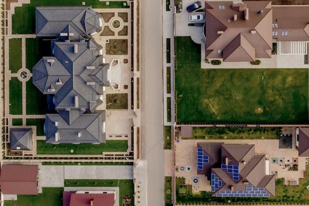Вид сверху на частный дом с мощеным двором и зеленой лужайкой с бетонным фундаментным полом.
