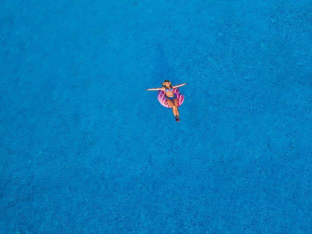 上からプールで美しい女の子の空中上面図、膨脹可能なリングドーナツで泳ぐのをリラックスし、家族での休暇中に水中で楽しんでください
