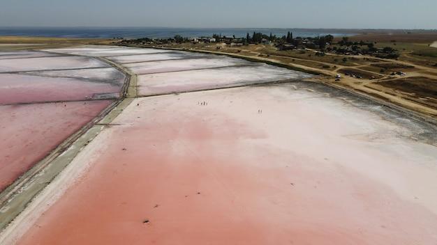 ピンクの水と美しい塩湖の空中上面図。飛んでいるドローンからのピンクの湖の眺め。上からのドローンヘリコプター写真。ドローンのある風景
