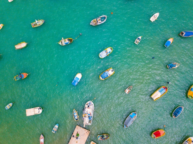 Вид сверху на красочные лодки в зеленой воде