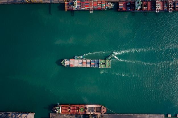 国際輸出入貨物ロジスティクス輸送ビジネスサービスと産業のための出荷港で海に浮かぶコンテナ船の空中上面図