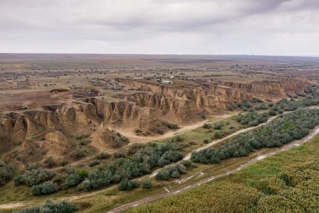 Вид сверху с воздуха на сельскую дорогу, разделяющую мельницу и песчаные дюны.