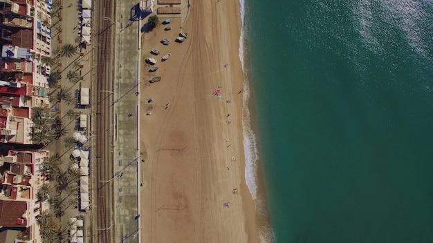Вид сверху на пустой песчаный пляж, синее море, железные дороги и крыши отелей, барселона, испания
