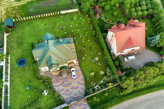 Вид сверху с высоты птичьего полета на гонтовую крышу дома и автомобиль на вымощенном дворе с зеленой лужайкой.