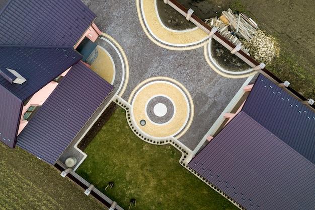 녹색 잔디와 기하학적 추상 패턴으로 다채로운 포장 된 마당의 배경에 집 지붕 널 지붕의 공중 평면도. 지붕, 수리 및 개조 공사.