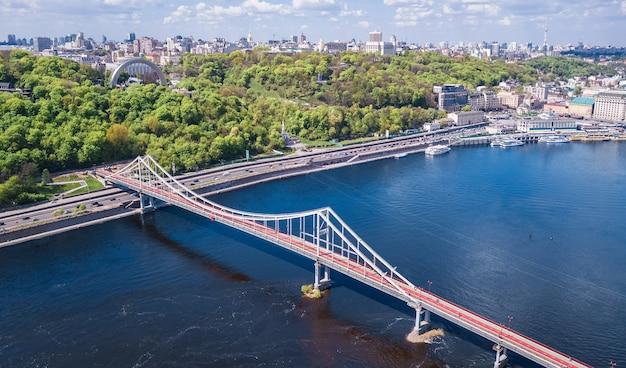 Вид сверху с воздуха на город киев сверху на горизонте киева, холмы, парковый мост и реку днепр