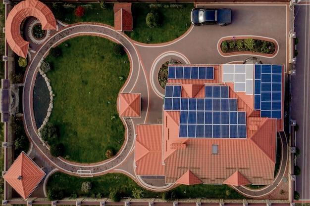 青いパネルと新しいモダンな住宅のコテージの空中上面図。再生可能なエコロジカルグリーンエネルギー生産コンセプト。