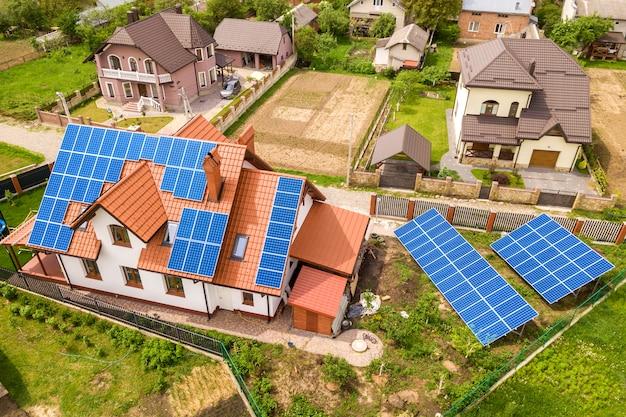 Воздушный взгляд сверху нового современного жилого коттеджа дома с голубой сияющей солнечной системой фотоэлектрических панелей на крыше. концепция производства экологически чистой зеленой энергии.