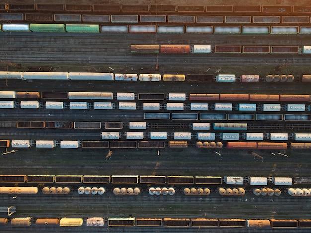 Вид сверху железнодорожных вагонов с воздуха. грузовые поезда на закате