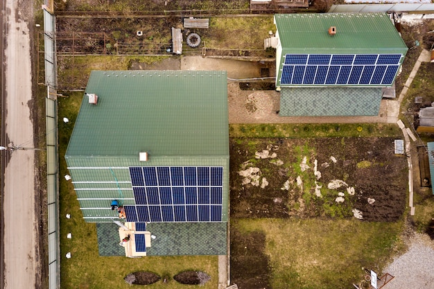 Воздушный взгляд сверху жилого дома при команда работников устанавливая солнечную систему фотоэлектрических панелей на крышу. концепция производства возобновляемой энергии.