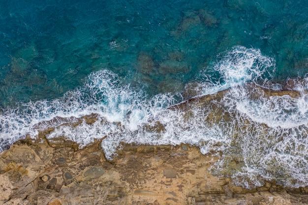 ロードス島ギリシャの岩に当たる海の波の空中上面図
