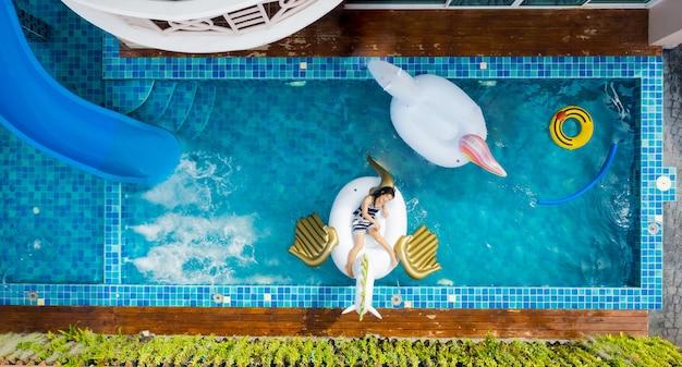 수영장의 공기 주입식 매트리스에서 휴식을 취하는 여성과 함께 수영장의 공중 전망