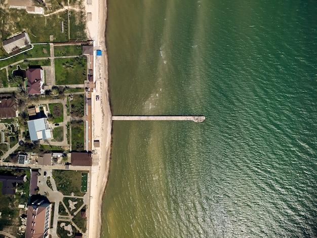 Вид сверху с воздуха на бирюзовую воду с бетонным пирсом на азовском море