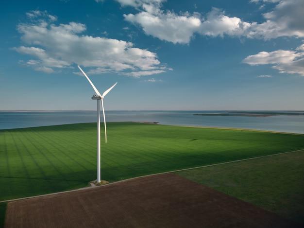 Вид сверху на ветряные турбины и сельское хозяйство на берегу моря на закате