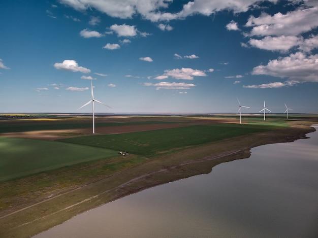 해질녘 바다 근처 풍력 터빈과 농업 분야의 공중 평면도