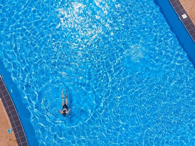 Вид сверху на женщину в бассейне с водой, концепция праздника тропических каникул, вид с дрона