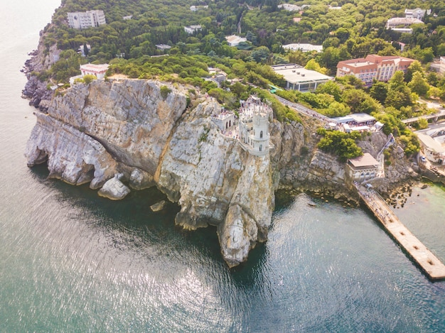 Aerial top view of old ancient beautiful castle on the edge of rock mountain on a sea coast