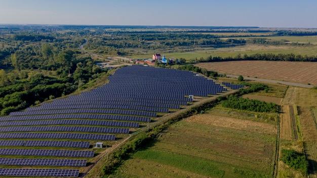 Вид сверху на солнечную электростанцию в зеленом поле в солнечный день