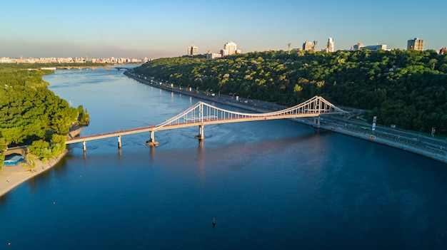 Aerial top view of pedestrian park bridge and dnieper river. city of kiev, ukraine