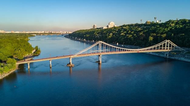 Aerial top view of pedestrian park bridge and dnieper river from above, city of kiev, ukraine