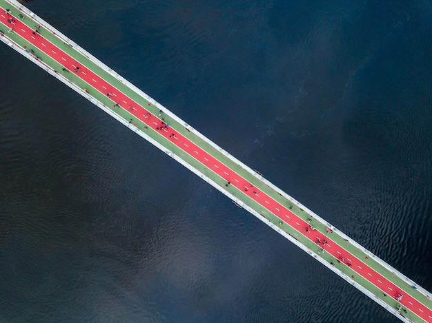 Aerial top view of people are walking on the pedestrian bridge and dnieper river from above in city kyiv