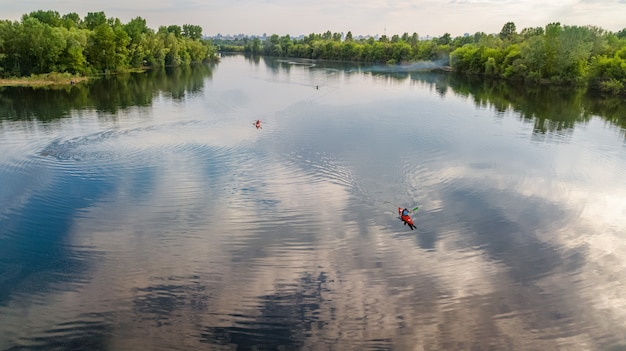 Aerial top view of people kayaking, man paddling in kayak on river canoe tour having fun, active weekend and vacation, outdoor water sport and nature concept