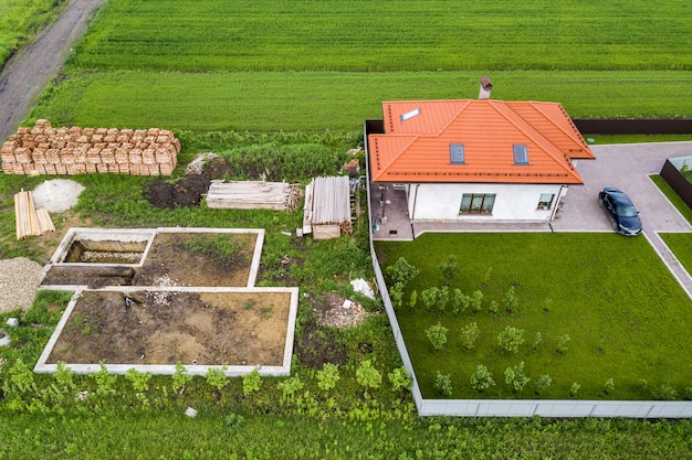 Aerial top view of a private house with attic windows on roof, paved yard with green grass lawn and building site with concrete foundation floor and stacks of yellow bricks for construction..