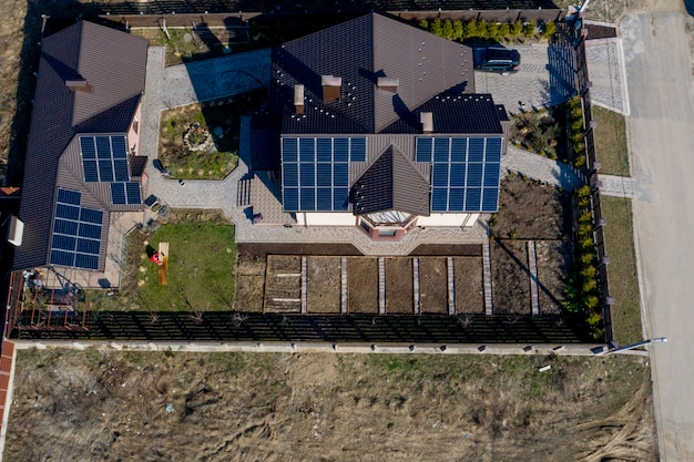 Aerial top view of a private house with paved yard with green grass lawn with concrete foundation floor