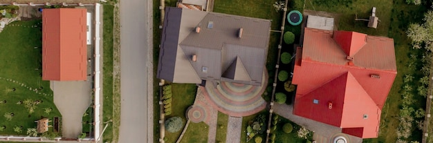 Aerial top view of a private house with paved yard with green grass lawn with concrete foundation floor.
