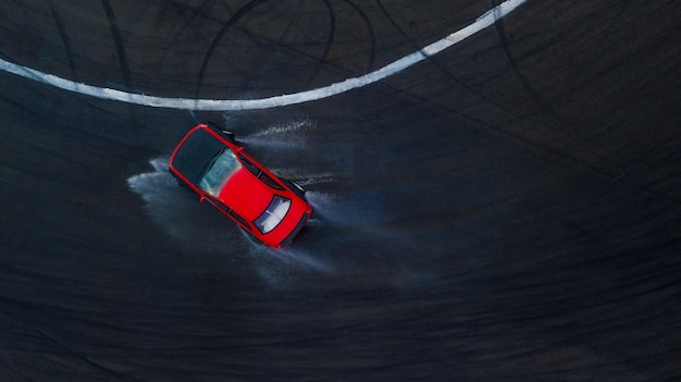 Aerial top view professional driver drifting car on wet race track, with water splash, red car.