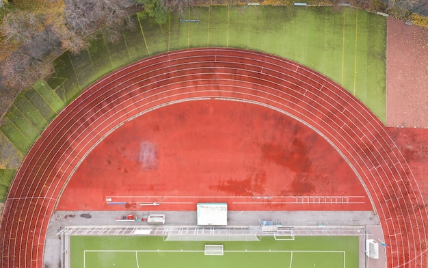 Aerial top view of red running tracks in the stadium without people
