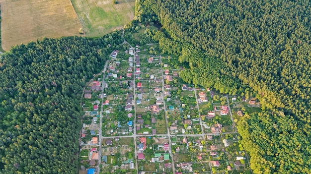 Aerial top view of residential area summer houses in forest from above, countryside real estate and small dacha village in ukraine