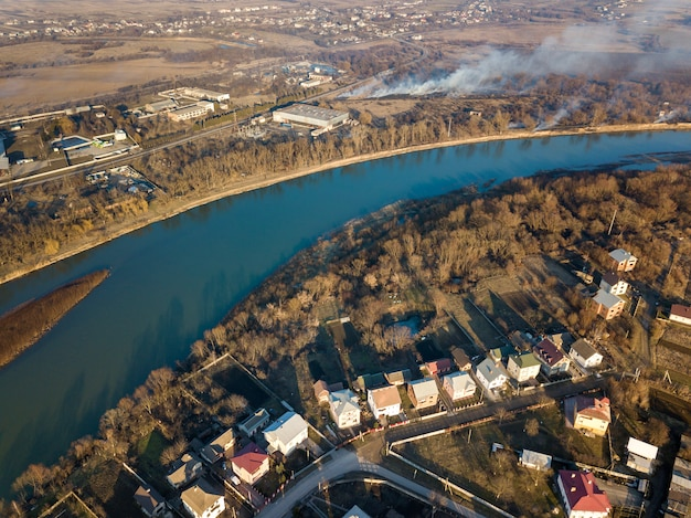 Aerial top view of river flowing through town. rural landscape of residential houses, roads and trees on spring or autumn day. drone photography.