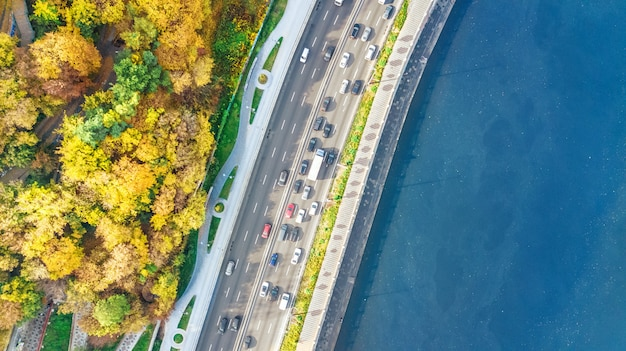 Aerial top view of road automobile traffic jam of many cars from above, dnipro river and kyiv autumn cityscape, city transportation concept