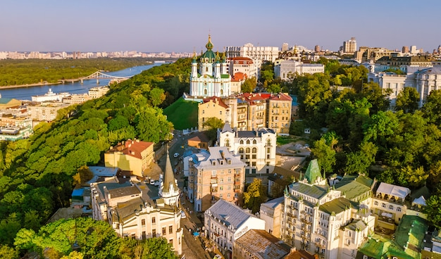 Aerial top view of saint andrew's church and andreevska street from above, cityscape of podol district on sunset, skyline of city of kiev, ukraine
