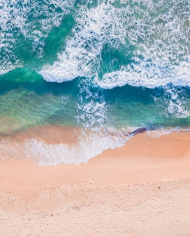 Aerial top view of sandy beach with stunning waves and turquoise water