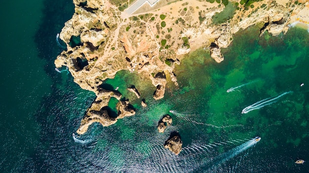 Aerial top view of scenic ponta da piedade of lagos, portugal. rugged seaside cliffs and aqua ocean waters in the algarve region of portugal
