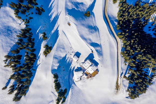 Aerial top view of small houses on a snowy mountain surrounded by trees in the daylight