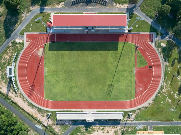 Aerial top view on a soccer field, grandstand, football field with red running track.