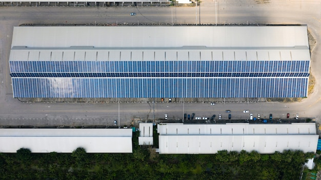 Aerial top view of the solar cells on the roof, solar panels installed on a roof of a large industrial building or a warehouse