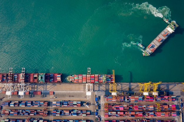 물류를 위해 크레인을 통해 컨테이너를 적재하기 위해 부두로 컨테이너 선박을 밀고있는 공중 평면도 예인선