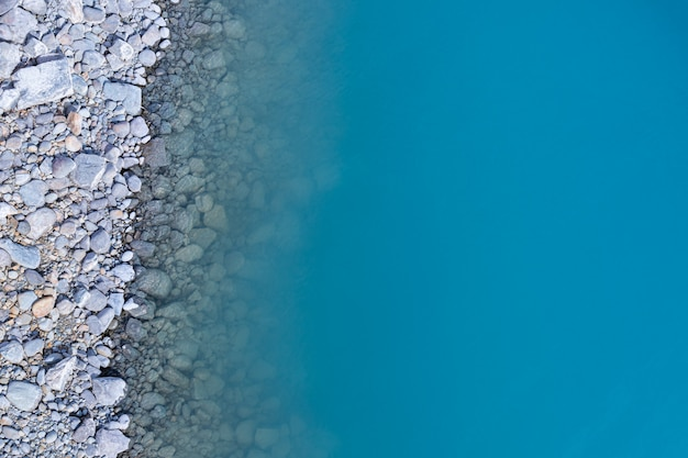Aerial top view of turquoise lake and rocks abstract background at tekapo, new zealand