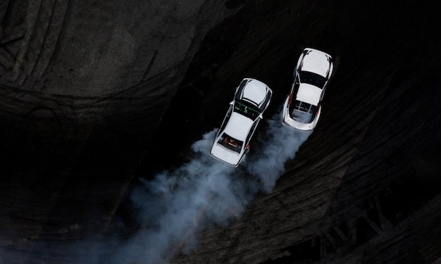Aerial top view two cars drifting battle on asphalt race track with lots of smoke.