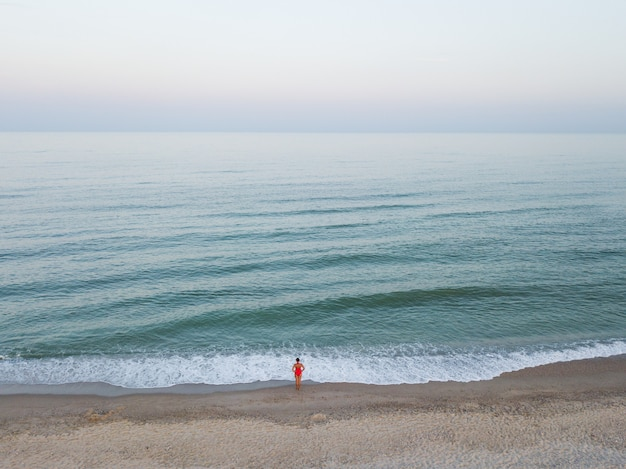 Aerial top view to woman in red bikini near by sea on the beach