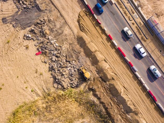 Aerial top view of yellow bulldozer work dig soil